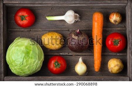 Ingredients for borscht, beetroot soup, beet soup: cabbage, carrots, onions, garlic, beets, tomatoes, potatoes in wooden box. Harvest vegetables. The concept of vegetarianism, vegan, healthy eating - stock photo