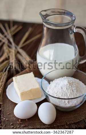 Ingredients for bread or dough preparation (wheat, eggs, milk, flour and butter) on wood table
