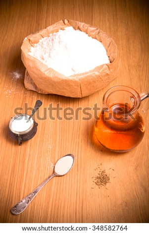 Ingredients for bread with saffron: flour, saffron water, yeast and salt on light wooden background. Toned.