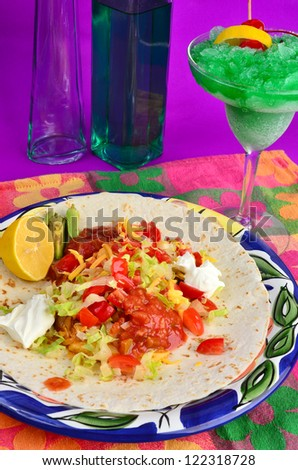 Ingredients for chicken fajita burrito on flour tortilla on colorful plate and place m mat with frozen cocktail and liquor bottles in background. Typical Mexican Restaurant setup. - stock photo