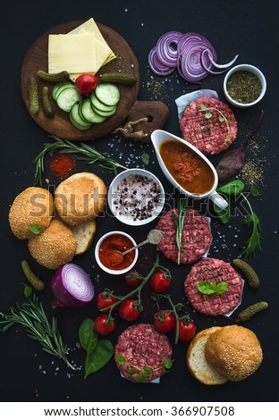 Ingredients for cooking burgers. Raw ground beef meat cutlets, buns, red onion, cherry tomatoes, greens, pickles, tomato sauce, cheese, herbs and spices over black background, top view - stock photo