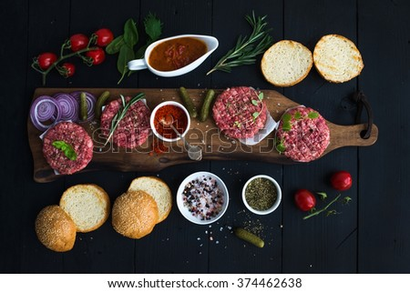 Ingredients for cooking burgers. Raw ground beef meat cutlets on wooden chopping board, red onion, cherry tomatoes, greens, pickles, tomato sauce, cheese, herbs, spices over black background, top view - stock photo