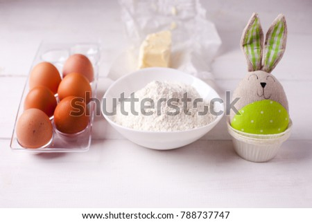 Ingredients for cooking dough, sweet baking. Bowl of flour, butter, eggs, baking molds and toy bunny, Easter spring background