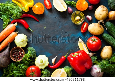 Ingredients for cooking. Fresh vegetables and spices on dark table with space for text. Healthy food. - stock photo