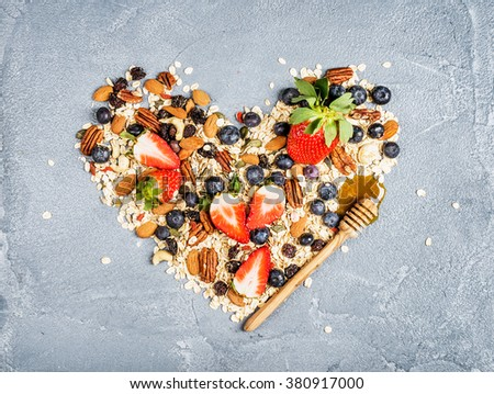 Ingredients for cooking healthy breakfast in shape of heart.  Strawberries, blueberries, nuts, oat flakes, dried fruits, honey with drizzlier over concrete textured background, top view - stock photo