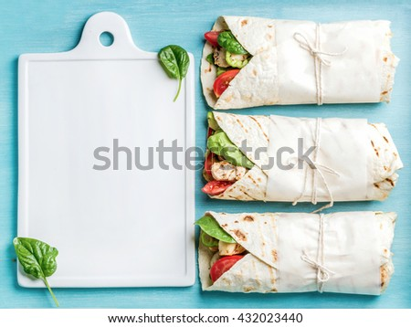 Ingredients for cooking healthy meat dinner. Raw uncooked beef steaks with vegetables, rice, spices and wine bottle over wooden background, cast iron grilling pan in center. Top view, copy space - stock photo