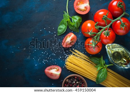 Ingredients for cooking Italian pasta - spaghetti, tomatoes, basil and oil. Top view with copyspace. Organic food. - stock photo