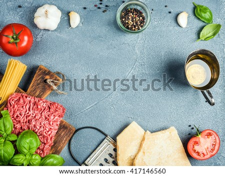 Ingredients for cooking pasta Bolognese. Spaghetti, Parmesan cheese,  tomatoes, metal grater, oil, garlic, minced meat, pepper and basil on grey concrete background, top view, copy space - stock photo