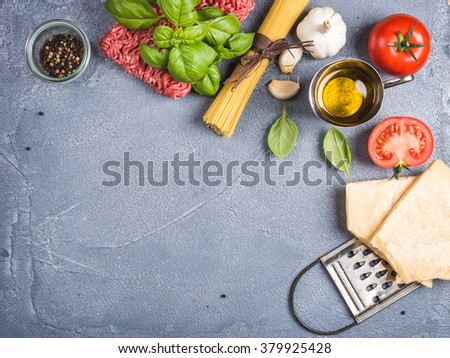 Ingredients for cooking pasta Bolognese. Spaghetti, Parmesan cheese,  tomatoes, metal grater, olive oil, garlic, minced meat, pepper and fresh basil on grey concrete background, top view, copy space - stock photo