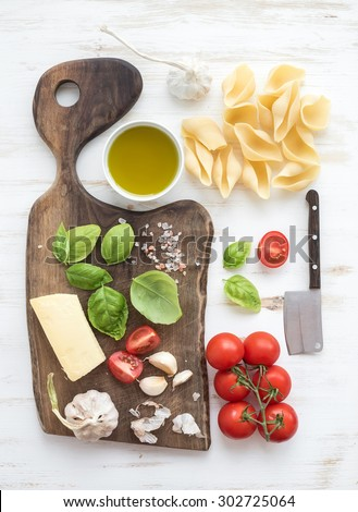 Ingredients for cooking pasta. Conchiglioni, basil leaves, cherry-tomatoes, Parmesan cheese, olive oil, salt, garlic on rustic walnut chopping board over white wooden background, top view - stock photo