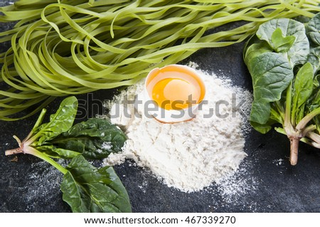 Ingredients for cooking pasta. Raw egg, pile of white wheat flour, spinach leaves and green raw pasta on black stone board background