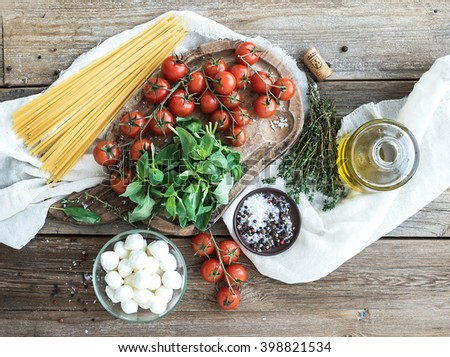 Ingredients for cooking pasta. Spaghetti, basil, cherry tomatoes, mozzarella, olive oil, thyme, spices on rustic board over wood background. Top view, horizontal - stock photo