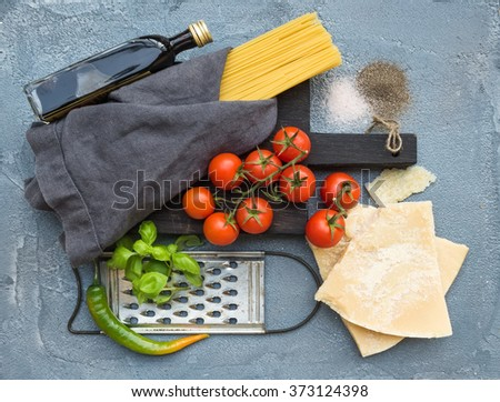 Ingredients for cooking pasta. Spaghetti on dark wooden board, Parmesan cheese, cherry tomatoes, metal grater, olive oil and fresh basil on grey concrete background, top view - stock photo