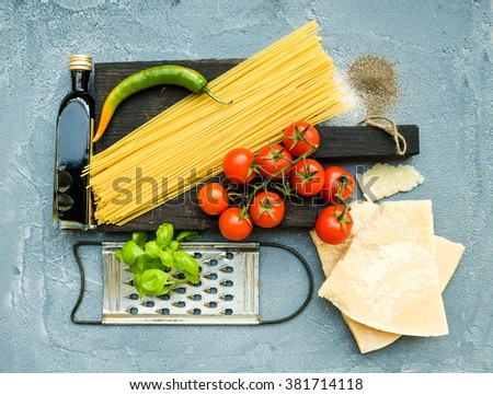 Ingredients for cooking pasta. Spaghetti on dark wooden board, Parmesan cheese, cherry tomatoes, metal grater, olive oil and fresh basil on grey-blue concrete background, top view - stock photo