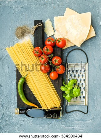Ingredients for cooking pasta. Spaghetti on dark wooden board, Parmesan cheese, cherry tomatoes, metal grater, olive oil and fresh basil on grey-blue concrete background, top view, vertical - stock photo