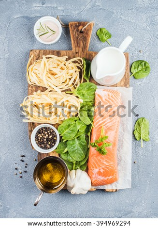 Ingredients for cooking pasta tagliatelle with salmon, spinach and cream on rustic wooden board over grey concrete textured background, top view - stock photo