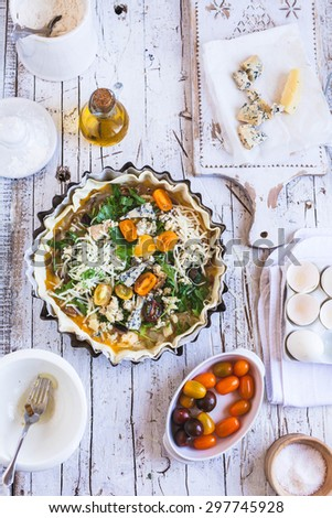 Ingredients for cooking pie, tart, quiche. Uncooked quiche over on white rustic wooden kitchen table with scattered ingredients. Rustic style .See series - stock photo