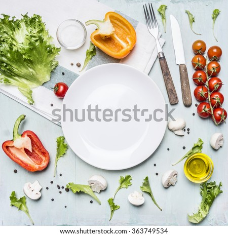 Ingredients for cooking salad cherry tomatoes, lettuce, peppers, spices and oil  laid out around a white plate on wooden rustic background top view close up - stock photo