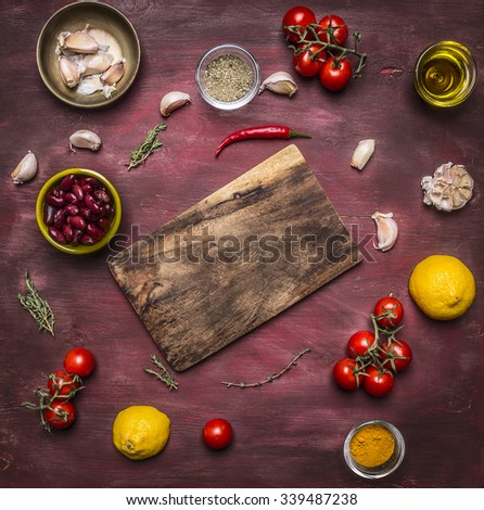 Ingredients for cooking vegetarian food tomatoes on a branch, lemon, olive oil, red hot pepper, herbs, cutting board , frame, with text area on wooden rustic background top view - stock photo