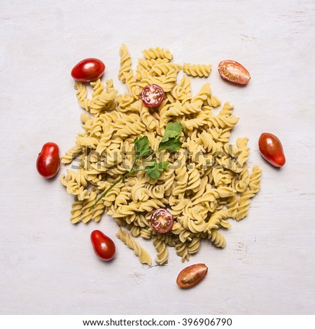 Ingredients for cooking vegetarian raw pasta with cherry tomatoes and parsley on wooden rustic background top view - stock photo