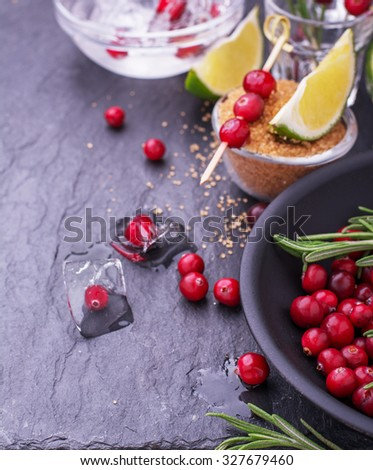 Ingredients for cranberry cocktail with lime and rosemary on a black stone plaque with glasses and a black bowl. Top view. selective Focus - stock photo