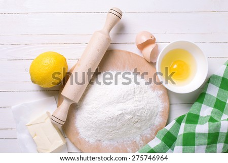 Ingredients for dough flour, egg, butter, lemon on white wooden background. Selective focus. - stock photo