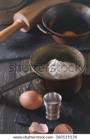 Ingredients for dough making. Flour, eggs in vintage copper bowls and salt with sieve and rolling-pin over old wooden table. Rustic style with retro filter effect