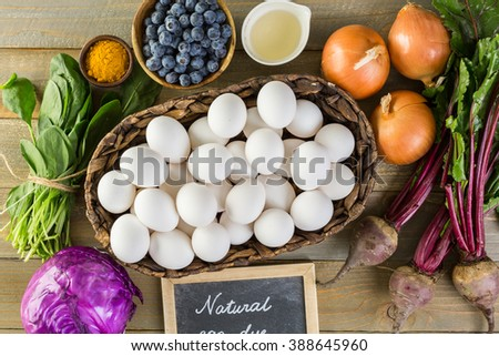 Ingredients for dyeing Easter eggs on a wood table.