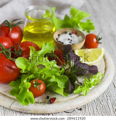 ingredients for fresh vegetable salad - tomatoes, garden herbs and olive oil - stock photo
