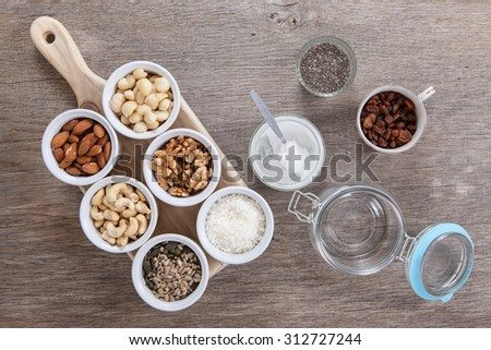 Ingredients for grain free granola: mixed nuts, seeds, raisins, coconut flakes, chia and coconut oil, selective focus - stock photo