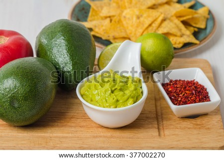 Ingredients for Guacamole and Guacamole dip on wooden background - stock photo