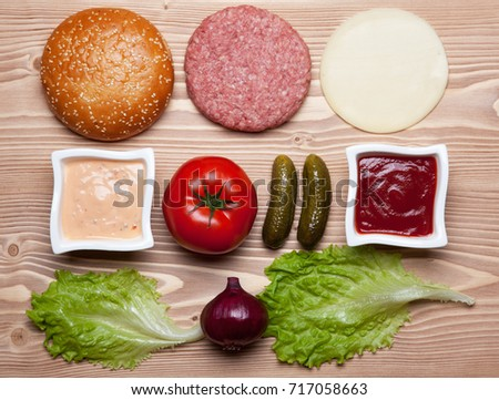 Ingredients for hamburger on wooden table.