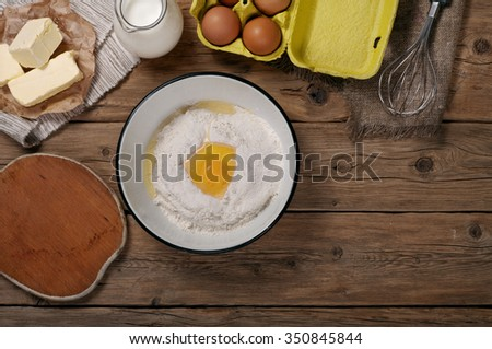 Ingredients for homemade dough (butter, egg, milk , flour). Ingredients for bakery products. Top view. Copy space. Free space for the object or text - stock photo