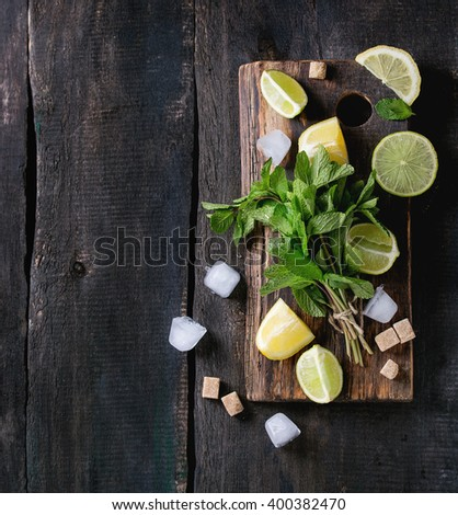 Ingredients for ice green tea lime, lemon, mint, sugar, green tea and ice cubes on wooden chopping board over old wooden background. Rustic style. Top view. With copy space - stock photo