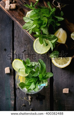 Ingredients for ice green tea lime, lemon, mint, sugar, green tea and ice cubes on wooden chopping board with coctail glass and black iron teapot over old wooden background. Flat lay - stock photo