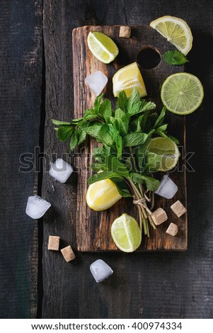 Ingredients for ice green tea lime, lemon, mint, sugar, green tea and ice cubes on wooden chopping board over old wooden background. Rustic style. Top view - stock photo