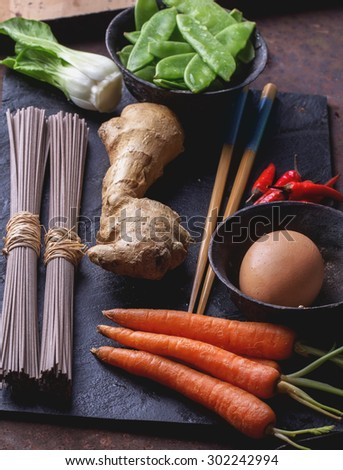 Ingredients for japanese soba stir fry: dry soba noodles, carrots, green pears, red chili, ginger, egg and chop sticks on the slate board - stock photo