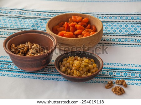 Ingredients for kutja (nuts, raisins, dried apricots) on embroidered tablecloth - stock photo