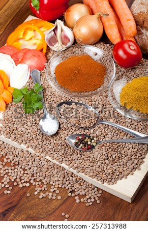ingredients for lentil soup on wooden table, with spice, vegetables, bread - stock photo