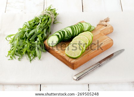 Ingredients for lime, cucumber, tarragon lemonade, cocktail on a white wooden background - stock photo