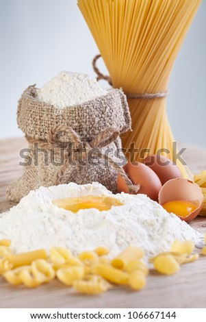 Ingredients for making pasta - flour and eggs on wooden table surface - stock photo