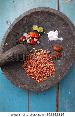 Ingredients for making peanut sauce with thick sweet soy sauce in a bowl over blue wooden table: peanuts, cayenne, salt, brown sugar, green lime - stock photo