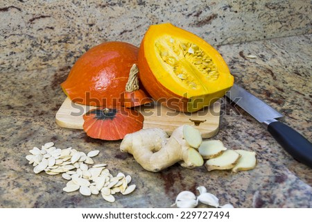 Ingredients for making pumpkin soup with a fresh halved autumn pumpkin, sliced root ginger, garlic cloves and seeds being prepared on a kitchen counter with copyspace - stock photo