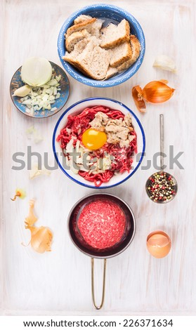 Ingredients for meat patties , ground raw beef, egg, soaked bun , onions, garlic on white wooden background, top view. - stock photo