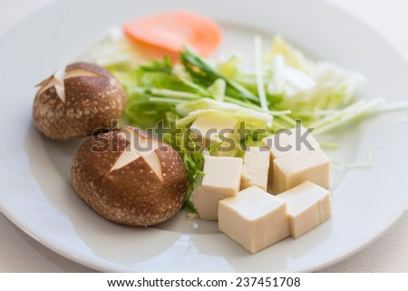 Ingredients for Mizutaki, a Japanese hot pot dish, including Chinese cabbage, mizuna (Japanese mustard), shiitake mushrooms, carrot, and two kinds of tofu  - stock photo