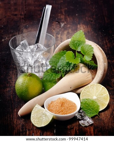 Ingredients for Mojito and Caipirinha. Mortar,Pestle and Lime. Brown sugar and an empty glass with straws - stock photo