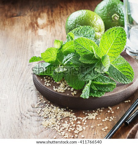 Ingredients for mojito fresh mint, lime and sugar on dark wooden board,selective focus. - stock photo
