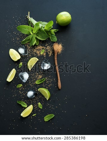 Ingredients for mojito. Fresh mint, limes, ice, sugar over black backdrop. Top view, copy space - stock photo