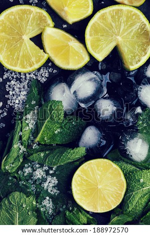 Ingredients for mojito (fresh mint, limes, ice, sugar) over black in retro filter effect. Top view. - stock photo