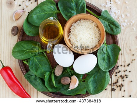 Ingredients for omlette preparation - eggs, spinach, parmesan cheese, pepper, olive oil, garlic, salt, pepper on light wooden table, selective focus. Top view - stock photo